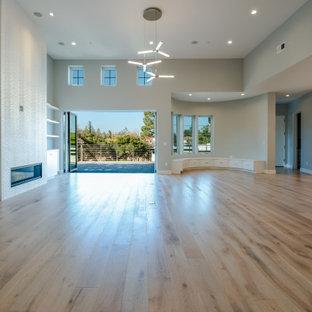 サンフランシスコの広いトランジショナルスタイルのおしゃれなLDK (フォーマル、グレーの壁、淡色無垢フローリング、標準型暖炉、タイルの暖炉まわり、埋込式メディアウォール、白い床) の写真