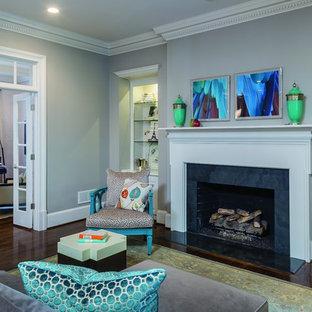 Modelo de salón para visitas abierto, clásico renovado, pequeño, sin televisor, con paredes grises, suelo de madera oscura, chimenea tradicional y marco de chimenea de baldosas y/o azulejos