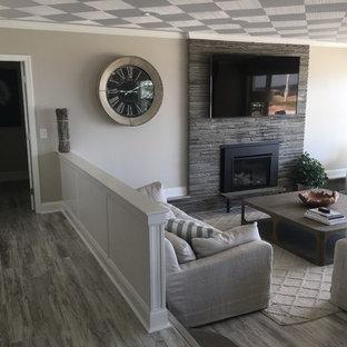 ボストンの中サイズのビーチスタイルのおしゃれなLDK (グレーの壁、濃色無垢フローリング、標準型暖炉、石材の暖炉まわり、壁掛け型テレビ、グレーの床) の写真
