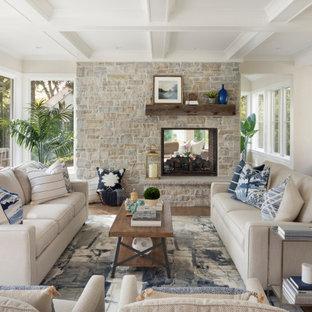 Réalisation d'un grand salon tradition ouvert avec un mur beige, un sol en bois brun, une cheminée double-face, un manteau de cheminée en pierre, une salle de réception et un plafond à caissons.