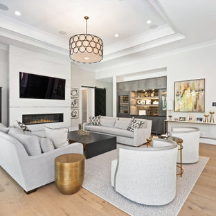 Living room - large transitional open concept light wood floor, brown floor and tray ceiling living room idea in Chicago with a bar, gray walls, a wall-mounted tv and a ribbon fireplace