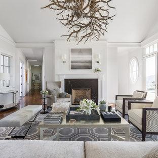 Esempio di un grande soggiorno chic aperto con sala formale, pareti bianche, pavimento in legno massello medio, camino classico, nessuna TV e cornice del camino in pietra