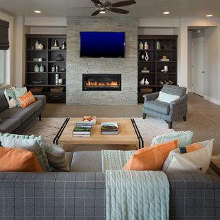 Modelo de salón abierto, clásico renovado, con paredes grises, suelo de madera en tonos medios, chimenea lineal, marco de chimenea de piedra y televisor colgado en la pared