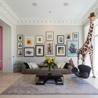 Example of a transitional light wood floor living room design in London with a music area and gray walls