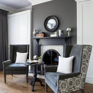 Inspiration pour un salon traditionnel avec un mur gris, un sol en bois brun et une cheminée standard.