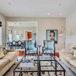 Immagine di un grande soggiorno tradizionale con pareti grigie, pavimento in legno massello medio, camino classico, cornice del camino in pietra, TV nascosta e pavimento rosso