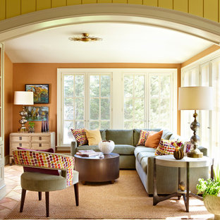 This is an example of a traditional enclosed living room in Other with orange walls.