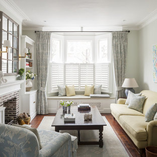 This is an example of a medium sized classic enclosed living room in London with a standard fireplace, a brick fireplace surround, green walls, no tv and medium hardwood flooring.