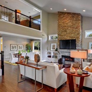 Пример оригинального дизайна: открытая гостиная комната в стиле современная классика с бежевыми стенами, фасадом камина из камня, телевизором на стене и стандартным камином