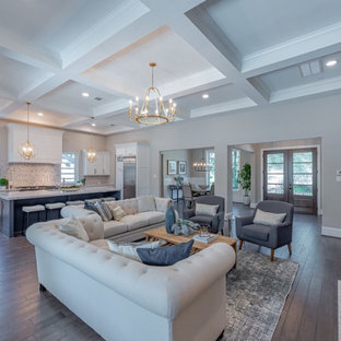 Geräumiges, Offenes Klassisches Wohnzimmer mit dunklem Holzboden, Kaminumrandung aus Holzdielen und Kassettendecke in Houston