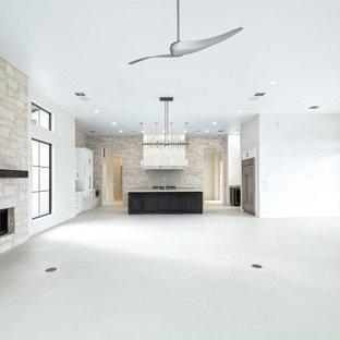 オースティンの広いトランジショナルスタイルのおしゃれなLDK (白い壁、磁器タイルの床、標準型暖炉、石材の暖炉まわり、壁掛け型テレビ、白い床) の写真