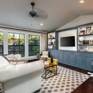 Diseño de salón abierto, clásico renovado, grande, sin chimenea, con suelo de madera oscura, televisor colgado en la pared, paredes multicolor y suelo marrón