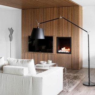 Modelo de salón para visitas abierto, actual, de tamaño medio, con televisor colgado en la pared, paredes blancas, suelo de madera clara, chimenea tradicional y suelo gris