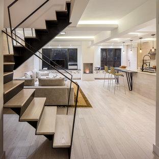 ニューヨークの中サイズのコンテンポラリースタイルのおしゃれなリビング (白い壁、淡色無垢フローリング、標準型暖炉、漆喰の暖炉まわり、据え置き型テレビ、ベージュの床) の写真