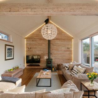 Modelo de salón nórdico con paredes blancas, suelo de madera en tonos medios, estufa de leña y suelo marrón