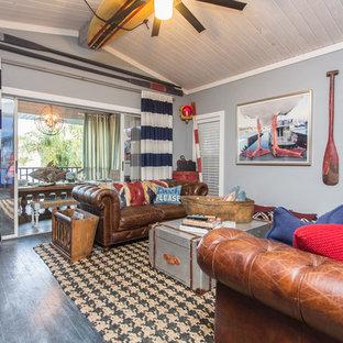 タンパの大きいビーチスタイルのおしゃれなリビング (マルチカラーの壁、塗装フローリング、コーナー設置型暖炉、木材の暖炉まわり、壁掛け型テレビ、黒い床) の写真