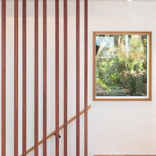 中サイズのビーチスタイルのおしゃれなLDK (白い壁、コンクリートの床、吊り下げ式暖炉、コンクリートの暖炉まわり、グレーの床) の写真