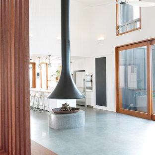 ニューカッスルの中サイズのビーチスタイルのおしゃれなLDK (白い壁、吊り下げ式暖炉、コンクリートの暖炉まわり、グレーの床) の写真