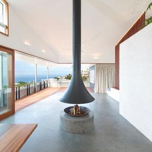 Idee per un soggiorno costiero di medie dimensioni e aperto con pareti bianche, camino sospeso, cornice del camino in cemento e pavimento grigio