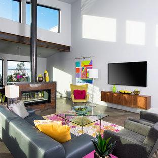 Esempio di un soggiorno contemporaneo di medie dimensioni e aperto con sala formale, pareti bianche, pavimento in cemento, camino bifacciale, cornice del camino in metallo e TV a parete