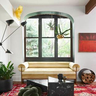 Foto di un soggiorno boho chic di medie dimensioni e aperto con pareti bianche, pavimento in legno massello medio, camino bifacciale, cornice del camino in intonaco, TV a parete e pavimento nero