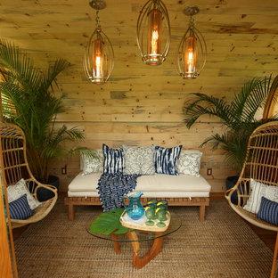 ハワイの小さいトロピカルスタイルのおしゃれな独立型リビング (ベージュの壁、無垢フローリング、暖炉なし、テレビなし、茶色い床) の写真