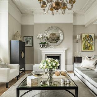 ロンドンの大きいトランジショナルスタイルのおしゃれな独立型リビング (フォーマル、ベージュの壁、淡色無垢フローリング、薪ストーブ、石材の暖炉まわり、テレビなし、茶色い床) の写真