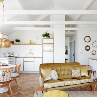 This is an example of an eclectic open plan living room in London with white walls, medium hardwood flooring and brown floors.