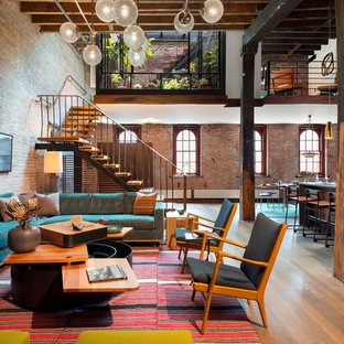 Inspiration for an industrial formal and open concept medium tone wood floor living room remodel in New York
