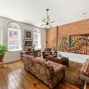 Example of an eclectic open concept medium tone wood floor living room design in New York with white walls