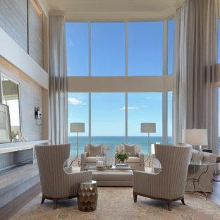Foto di un grande soggiorno costiero aperto con sala formale, pareti bianche, parquet chiaro, camino lineare Ribbon, cornice del camino in pietra e nessuna TV