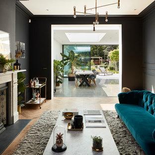 ロンドンのトランジショナルスタイルのおしゃれな独立型リビング (黒い壁、淡色無垢フローリング、標準型暖炉、石材の暖炉まわり、テレビなし) の写真
