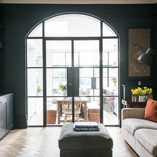 Foto di un soggiorno tradizionale con pareti nere, pavimento in legno massello medio e TV a parete