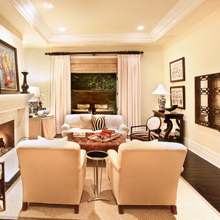 Example of a mid-sized tuscan enclosed dark wood floor living room design in Orange County with beige walls and a standard fireplace