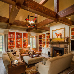 Photo of a mid-sized traditional open concept living room in Philadelphia with a library, a standard fireplace, beige walls, medium hardwood floors and a built-in media wall.