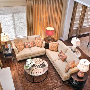 Esempio di un grande soggiorno tropicale chiuso con pareti beige, pavimento in legno massello medio, camino classico, cornice del camino in intonaco e nessuna TV