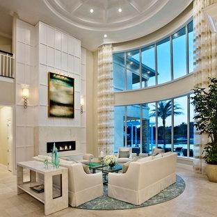 マイアミの大きいトロピカルスタイルのおしゃれなLDK (フォーマル、ベージュの壁、横長型暖炉、トラバーチンの床) の写真