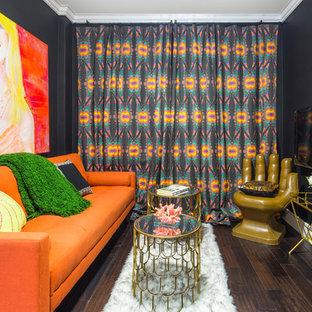 マイアミのトロピカルスタイルのおしゃれな独立型リビング (黒い壁、濃色無垢フローリング、壁掛け型テレビ、茶色い床) の写真
