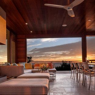 ボストンの大きいビーチスタイルのおしゃれなLDK (ベージュの壁、標準型暖炉、タイルの暖炉まわり、テレビなし、磁器タイルの床) の写真