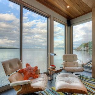 シアトルの小さいビーチスタイルのおしゃれなLDK (白い壁、磁器タイルの床、標準型暖炉、漆喰の暖炉まわり、茶色い床) の写真