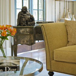 Masters Residence - This living room features a palette of gold, copper and neutrals in a variety of textures. A detail of a bronze Buddha statue, as well as an antique mirrored 1940s French desk, is seen here.