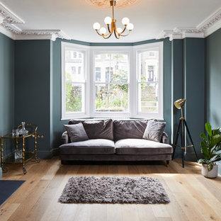 ロンドンのトランジショナルスタイルのおしゃれなリビング (緑の壁、無垢フローリング、標準型暖炉、茶色い床) の写真