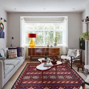 ロンドンのサンタフェスタイルのおしゃれな独立型リビング (白い壁、標準型暖炉、壁掛け型テレビ、ベージュの床) の写真