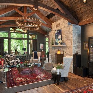 他の地域のラスティックスタイルのおしゃれなLDK (黒い壁、無垢フローリング、標準型暖炉、石材の暖炉まわり、茶色い床) の写真