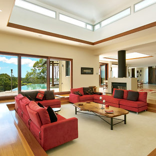 Medium sized modern open plan living room in Brisbane with beige walls, medium hardwood flooring and a standard fireplace.
