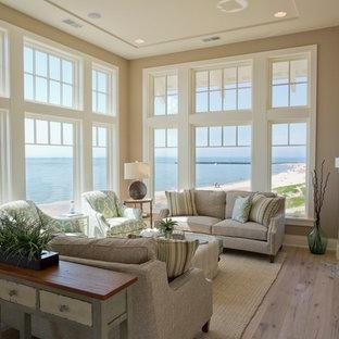 Immagine di un grande soggiorno stile marino aperto con pareti beige, parquet chiaro, camino classico e cornice del camino in pietra