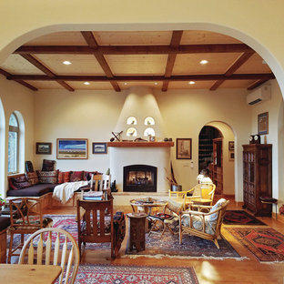Design ideas for a mid-sized open concept living room in Other with yellow walls, laminate floors, a standard fireplace, a plaster fireplace surround and no tv.