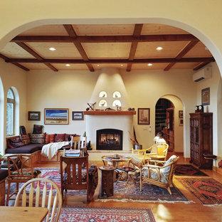 Idee per un soggiorno stile americano di medie dimensioni e aperto con pareti gialle, pavimento in laminato, camino classico, cornice del camino in intonaco e nessuna TV