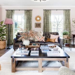 Imagen de salón abierto, tradicional renovado, grande, con paredes rosas, suelo de madera oscura y marco de chimenea de metal