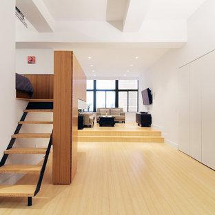 Diseño de salón tipo loft, minimalista, pequeño, con paredes blancas, suelo de bambú y televisor colgado en la pared